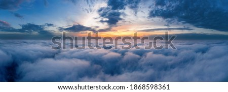 Beautiful dramatic sunset sky above fluffy clouds early in the morning from aerial drone view. Royalty-Free Stock Photo #1868598361