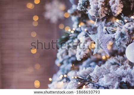 beautiful tender colorful festive background. Silver star close-up on Decorated snowy Christmas tree branch. New year mood. Shine sequins glitter. Place for text banner. postcard screensaver.