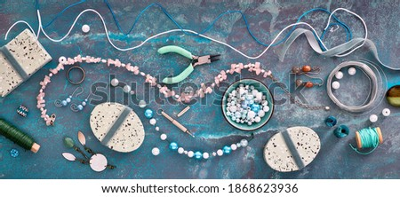 Making handmade jewelry for friends as Christmas gifts. Flat lay on dark textured background. Creative flat lay, panoramic composition. DIY craft hobby. Royalty-Free Stock Photo #1868623936