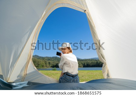 Young Asian woman in a T-shirt, shorts, and a bucket hat sitting in a camping tent looking back and smiling at a camera while taking a picture of a beautiful landscape in front of her with smartphone.
