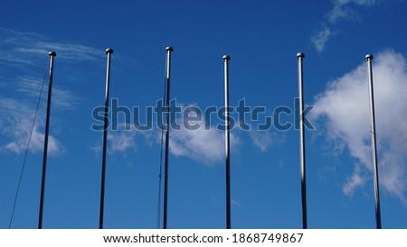 empty flagpoles against sky background Royalty-Free Stock Photo #1868749867