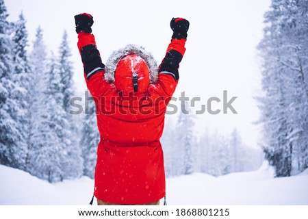 Back view of anonymous person in red outerwear raising clenched fists and celebrating victory on cold winter day near forest in Norway Royalty-Free Stock Photo #1868801215