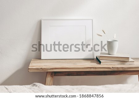 Horizontal white frame mockup on vintage wooden bench, table. Ceramic mug with dry Lagurus ovatus grass and books. White wall background. Scandinavian interior room design. Selective focus. Royalty-Free Stock Photo #1868847856