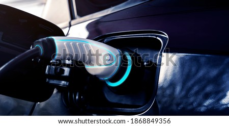 Power cable pump plug in charging power to electric vehicle EV car with modern technology UI control information display, car fueling station connected power cable alternative sustainable eco energy Royalty-Free Stock Photo #1868849356