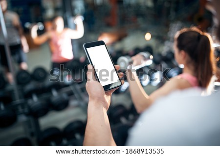 personal online workout with mobile phone or smartphone app at gym Royalty-Free Stock Photo #1868913535
