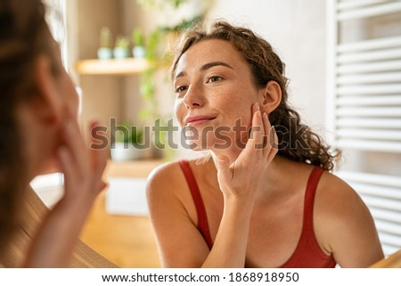 Beauty girl looking at mirror while touching her face and checking pimple, wrinkles and bags under the eyes, during morning beauty routine. Happy smiling beautiful young woman applying moisturizer.  Royalty-Free Stock Photo #1868918950