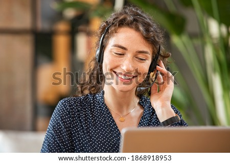 Happy young woman working on laptop while talking to customer on phone. Consulting corporate client in conversation with customer using computer. Service desk consultant talking in a call center. Royalty-Free Stock Photo #1868918953