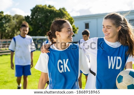 Two girls talking to each other after football training. Cheerful college players in conversation after sport match. Soccer players hugging and appreciating performance of the teammate after the match Royalty-Free Stock Photo #1868918965