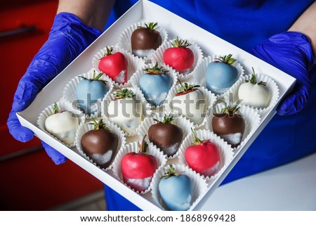 A woman holds in her hands a box of chocolate covered strawberries, dessert for Valentine's Day, romance, food as a gift. Homemade red strawberries in chocolate. A romantic dessert as a gift. Royalty-Free Stock Photo #1868969428
