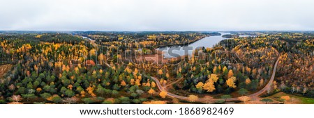 Panoramic aerial view of lake and colorful forests on a autumn day in Finland. Drone photography