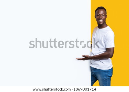 Handsome black man showing blank advertisement board, standing on yellow studio background. Smiling african american guy posing next to big white placard for text or advertising, panorama Royalty-Free Stock Photo #1869001714