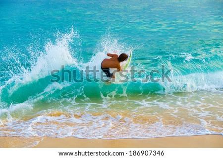 Teenage boy skim boarding on the tropical island of Maui, Hawaii, USA #186907346