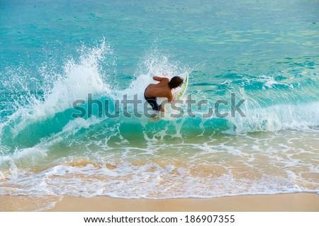 Teenage boy skim boarding on the tropical island of Maui, Hawaii, USA #186907355