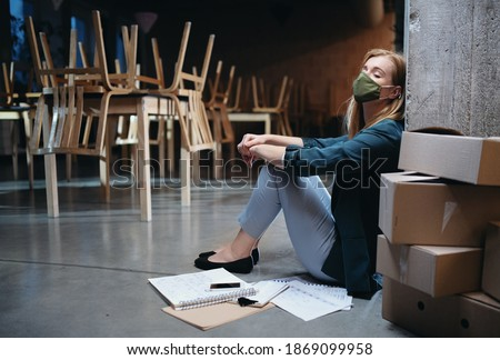 Tired owner sitting on floor in closed cafe, small business lockdown due to coronavirus. Royalty-Free Stock Photo #1869099958