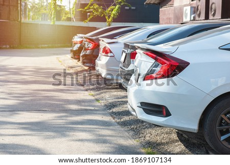 Close-up back view of white modern car with black trunk of row of cars and vans parked on asphalt on bright sunny day. Transportation and parking concept. Royalty-Free Stock Photo #1869107134