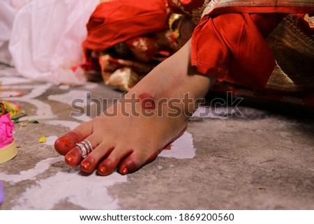 Close up picture of new bride feet decorated with red color ( Alta ). The feet of new bride wearing rings. Beautiful composition of new Bengali bride feet. Selective focus concept.