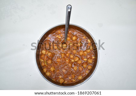 picture of punjabi chickpeas masala curry sabji in round vessel with spoon and black background .