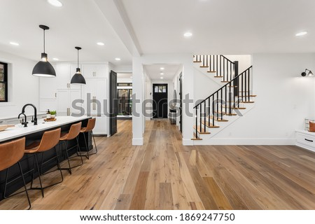 Kitchen and living room interior in new luxury home with open concept floor plan. Features large island with farmhouse sink, hardwood floors, and stairs to second story.  Royalty-Free Stock Photo #1869247750