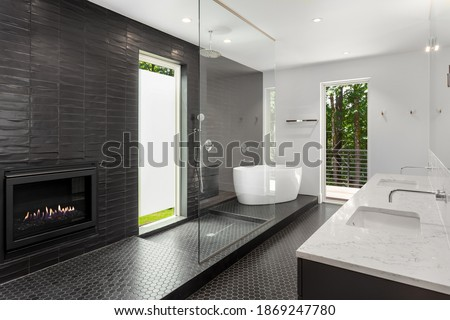 Bathroom in luxury home with large walk-in shower, double vanity, sinks, and tile floor. Also shows large soaking bathtub Royalty-Free Stock Photo #1869247780