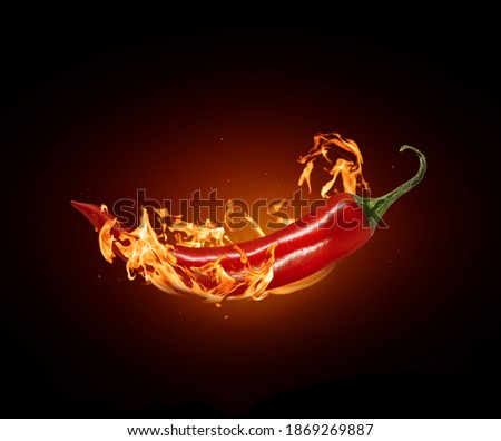 Red chili pepper close-up in a burning flame on a black  Royalty-Free Stock Photo #1869269887