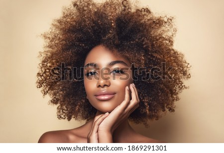 Beauty portrait of african american girl with clean healthy skin on beige background. Smiling dreamy beautiful black woman.Curly hair in afro style Royalty-Free Stock Photo #1869291301