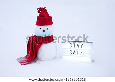 Snowman wearing a medical face mask, winter hat. scarf on a white background and lightbox with text . Stay safe. Christmas concept. Protection from infectons. Copy space. 2021