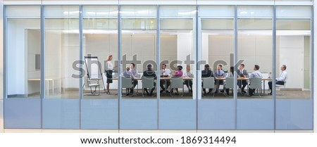 Wide shot through an office window with a businesswoman in a meeting with her employees. Royalty-Free Stock Photo #1869314494