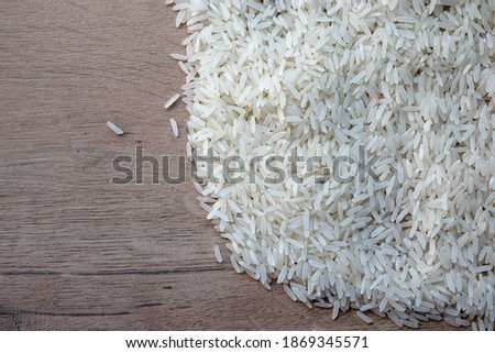A handful of white rice on a wooden table. Unboiled rice grains #1869345571