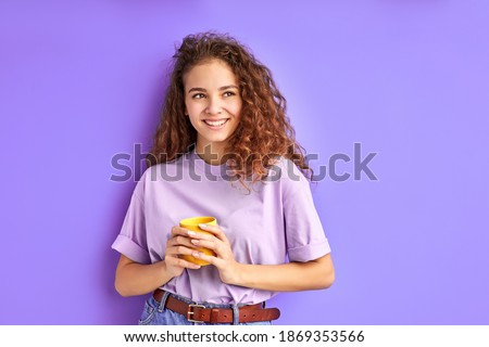 cute positive girl drinking coffee in the morning before school or university, stand looking away, isolated over purple background