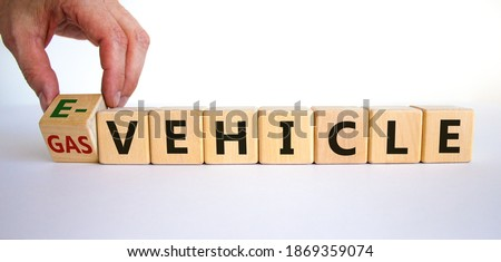 Gas vehicle or e-vehicle. Hand turns a cube and changes words 'gas vehicle' to 'e-vehicle'. Beautiful yelow table, white background, copy space. Business and electric vehicle concept. #1869359074