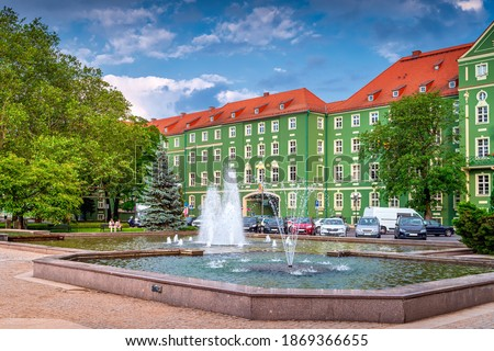 Green buildings of Szczecin City Council with red rooftops. Fountains in a pond and green trees on Jasne Blonia square, Stettin, Poland Royalty-Free Stock Photo #1869366655