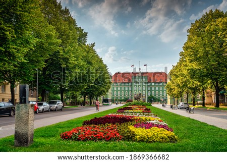 Colourful flowerbeds and tress on avenue of Pope John Paul II with green buildings of Szczecin City Council in the background Royalty-Free Stock Photo #1869366682