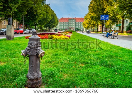 Traditional hydrant with gryphon head from Stettin city emblem, blurred flowerbed and town hall in background. Gryphon in Szczecin emblem since 1360 Royalty-Free Stock Photo #1869366760