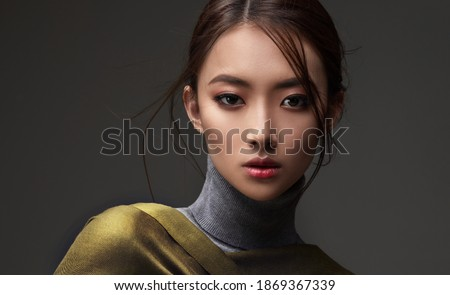 Beautiful Asian woman in a green shawl. Beauty of mysterious Chinese girl with flowing hair. Fashion, clothing and cosmetics Royalty-Free Stock Photo #1869367339