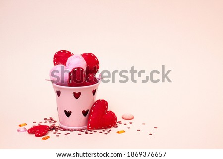 Small pink bucket with felt red and pink hearts on a pink background with shiny decor. Love, valentine day, birthday, mathers day holiday  and romantic concept. Place for text.