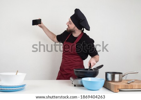 Chef guy takes pictures of himself on the phone. Cook takes a selfie in kitchen. Chef removes cooking process of the phone. Cook is broadcasting live. Blogger is cooking something. Chef recommended