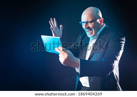 A man with a tablet in his hands is very happy. Concept - happy man with a tablet. Concept - man found out the good news. Businessman was told the news via video. Investor learned about stock growth