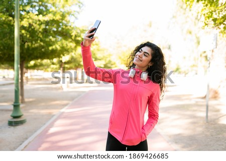 Good-looking woman in her 20s is taking a selfie with her smartphone after her workout run outdoors
