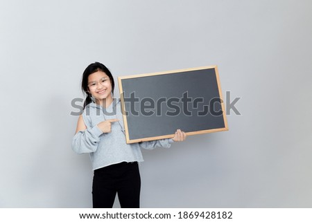 A little girl holds a blank chalkboard place for notification. Read this notification. Informing about the event. Cute schoolgirl with blackboard. Advertisement.