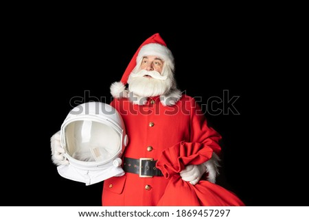 Santa Claus holds an astronaut's helmet in his hands and looks into the space. far. Close-up on a black background.