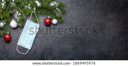 Funny christmas greeting card with decorated fir tree and medical face mask. Flat lay with copy space for your pandemic