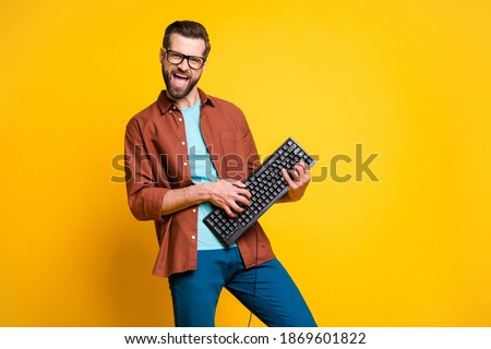 Photo portrait of bearded man keeping keyboard playing like guitar isolated on bright yellow color background