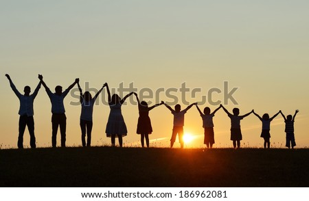 People silhouettes on sunset meadow having fun Royalty-Free Stock Photo #186962081