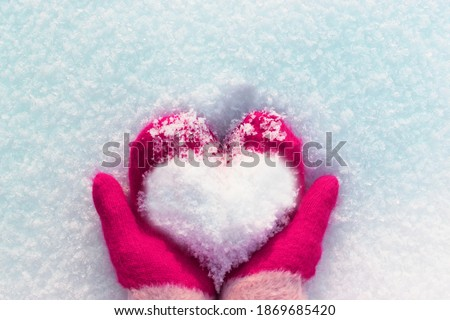hands in knitted mittens with a heart made of snow on a winter day. ... Snowy heart in hands. Human hands in warm red mittens with a snowy heart on a background of snow. Love winter christmas or Royalty-Free Stock Photo #1869685420