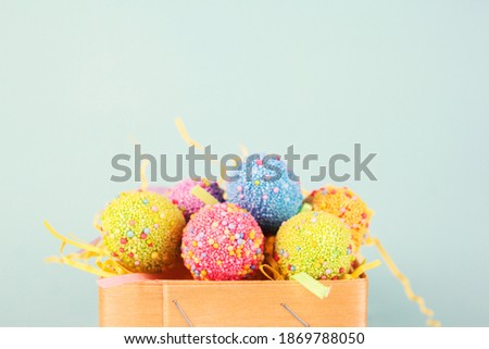Easter eggs in egg cartoon box on blue background close up. Festive decorations. Happy Easter.