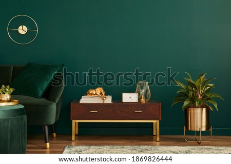 Luxury interior with stylish velvet sofa, wooden commode, pouf, plants, carpet, gold decoration, copy space and elegant personal accessories. Modern living room in classic house. Template. Royalty-Free Stock Photo #1869826444