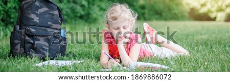 Caucasian school girl lying in park doing school homework. Child kid reading book and writing with pencil outdoor. Self education learning studying. Homeschooling for children. Web banner header.