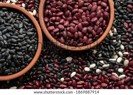 beans in brown ceramic bowl. bowl of beans. black bean, red kidney bean and white bean. navy, cannellini, white kidney bean on background made from beans and scattered various beans #1869887914