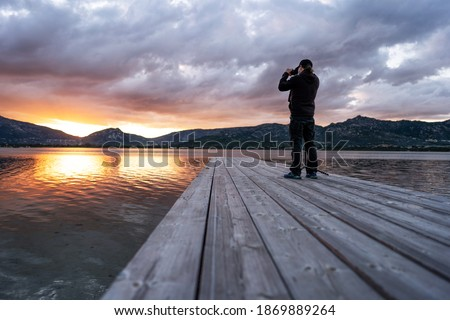 Photographing nature to spend more time outdoors and live better - A photographer standing on an old wooden pier takes a picture of a beautiful cloudy sunset with and sun setting between the mountains