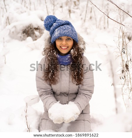 Beautiful happy laughing young woman in a winter hat with gloves and a scarf covered with snow flakes. Winter forest landscape background.